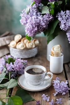 Chifres de xícara de café e bolo de massa folhada com creme de baunilha em uma caixa de metal na primavera ainda vida com um buquê de lilases em uma mesa de madeira