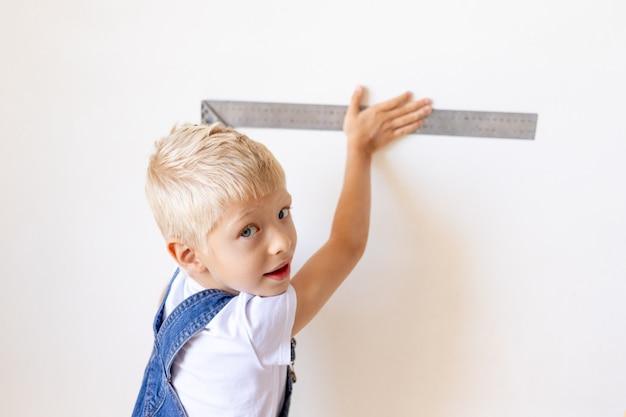 Child builder mede uma parede branca com uma régua de construção, conceito de construção e reparo