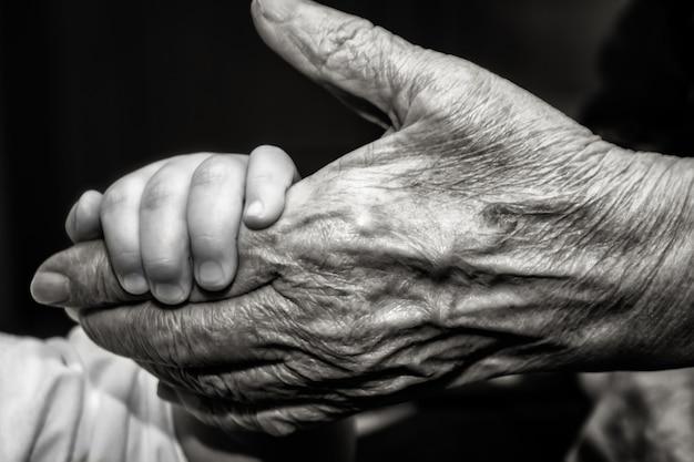 Childs mão e velho dedo de palma da pele enrugada