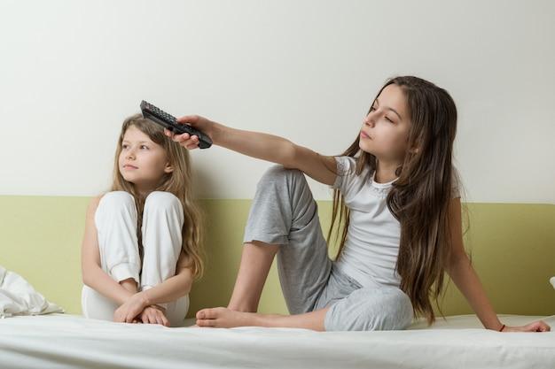 Childs meninas estão sentadas em casa na cama e assistindo tv