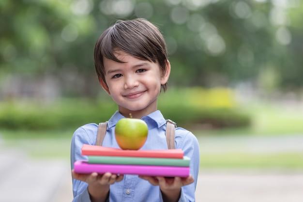 Childs segurando maçãs e livro pronto para ir para a escola novamente