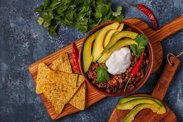 Chili com carne em uma tigela com abacate e creme de leite.