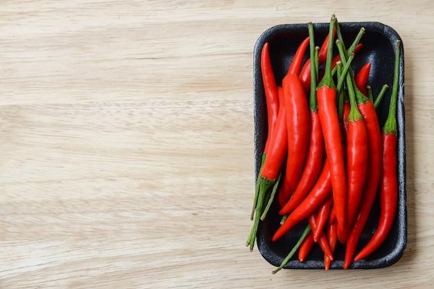 Chilli peppers na placa de plástico preta com madeira brilhante
