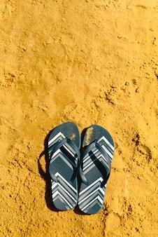 Chinelo azul marinho na praia de areia amarela