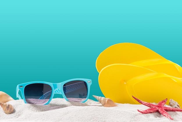 Chinelos amarelos na praia contra um fundo azul.
