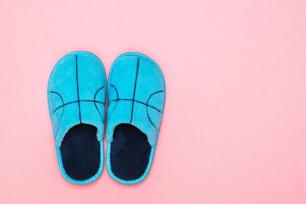Chinelos azuis com bordado na superfície rosa. sapatos confortáveis para casa