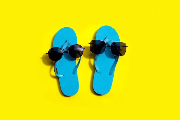 Chinelos azuis com óculos de sol em fundo amarelo. aproveite o conceito de férias de verão.