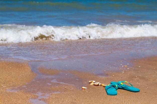 Chinelos azuis ficar na areia à beira-mar