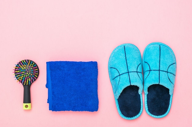 Chinelos azuis, toalha e pente em fundo rosa. conjunto de acessórios de manhã.