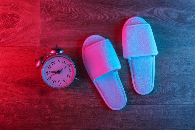Chinelos brancos e despertador no chão de madeira com brilho gradiente de néon vermelho-azul