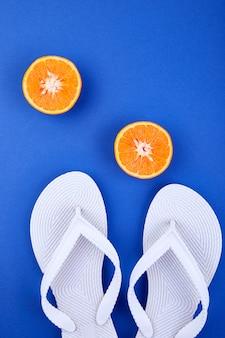 Chinelos brancos, fruta laranja, concha