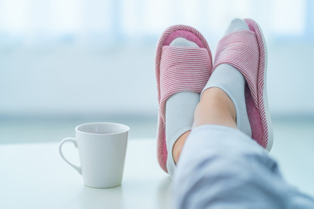 Chinelos caseiros confortáveis e macios nas pernas femininas