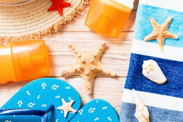 Chinelos, chapéu de palha, estrela do mar e protetor solar garrafa de fundo