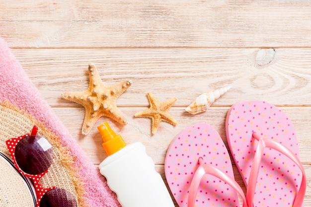 Chinelos, chapéu de palha, estrela do mar, protetor solar, spray de loção para o corpo na vista superior da parede de madeira. apartamento leigos verão praia mar acessórios parede, conceito de férias