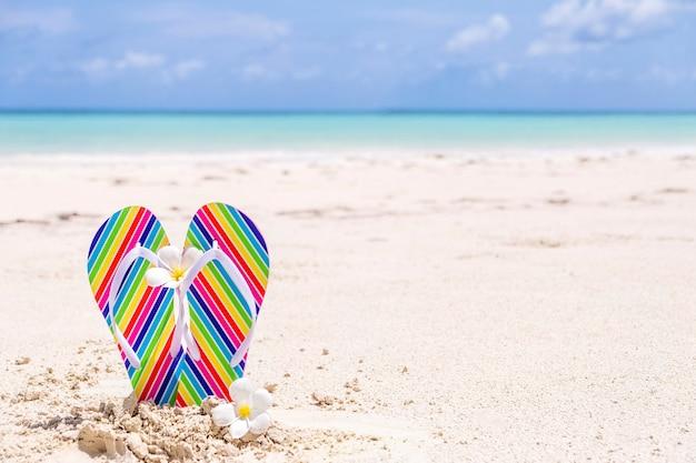 Chinelos coloridos em uma praia tropical ensolarada com águas azul-turquesa