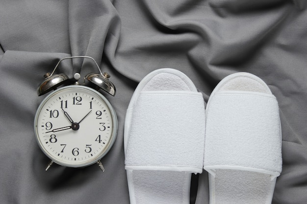 Chinelos de dormir branco hotel e despertador na colcha cinza.