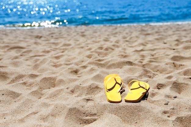 Chinelos de praia amarela na praia, verão, banho
