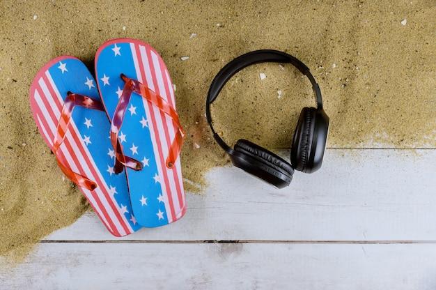 Chinelos de praia bandeira americana areia fones de ouvido de praia em fundo de madeira velho