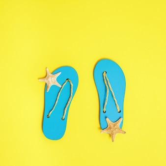 Chinelos de praia e pequenas estrelas do mar em papel amarelo brilhante