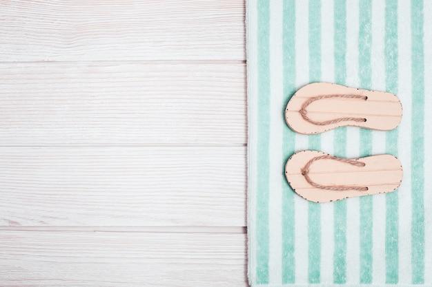 Chinelos de praia e toalha de algodão às riscas