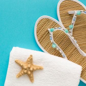 Chinelos de verão close-up com estrela do mar e toalha