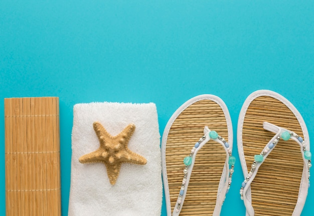 Chinelos de verão vista superior com toalha e estrela do mar