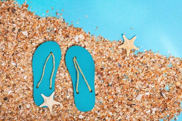 Chinelos e areia da praia em fundo azul