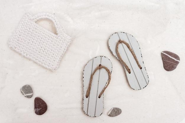 Chinelos e bolsa branca na praia