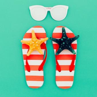 Chinelos e óculos de sol. período de férias. verão. estilo de praia mínimo