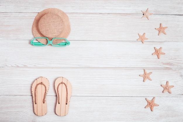 Chinelos, estrela do mar, óculos de sol, chapéu amarelo do sol em madeira branca