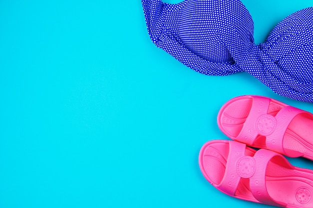 Chinelos, maiô, toalha em um fundo azul pastel