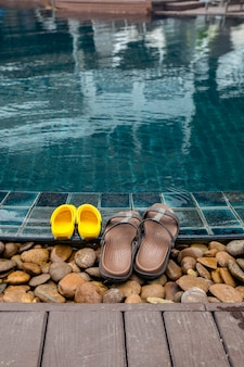 Chinelos na beira da piscina