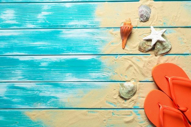 Chinelos no chão de madeira azul.