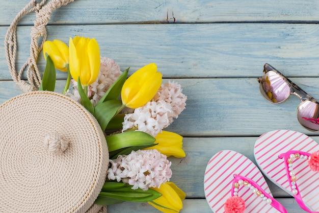Chinelos, óculos de sol, bolsa redonda de vime para mulheres e um buquê de tulipas e jacintos