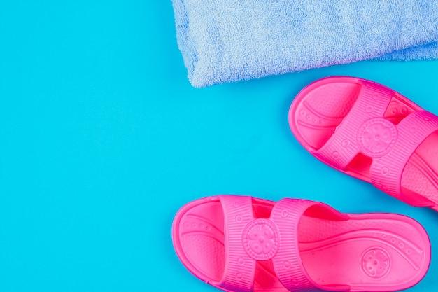 Chinelos, toalha em um fundo azul pastel