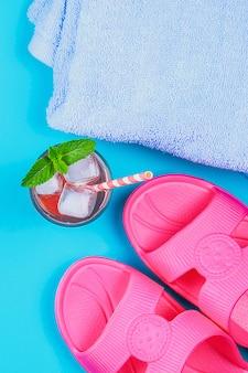 Chinelos, uma toalha e um cocktail de gelo