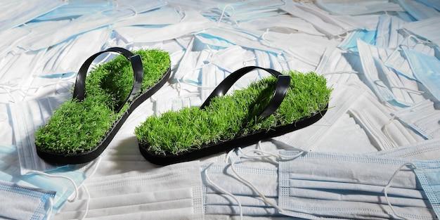 Chinelos verdes, com imitação de grama na superfície das máscaras médicas que poluem o planeta