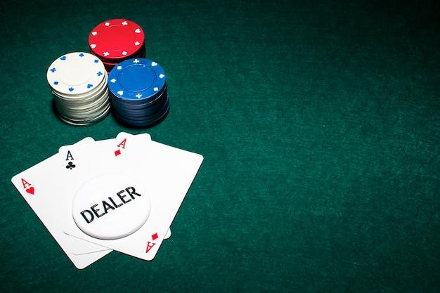 Chip de dealer sobre o cartão de ases e a pilha de fichas de cassino em fundo verde de pôquer