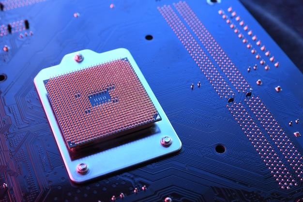 Chip do processador cpu do computador na placa de circuito, plano de fundo da placa-mãe. fechar-se. com iluminação vermelho-azulada.