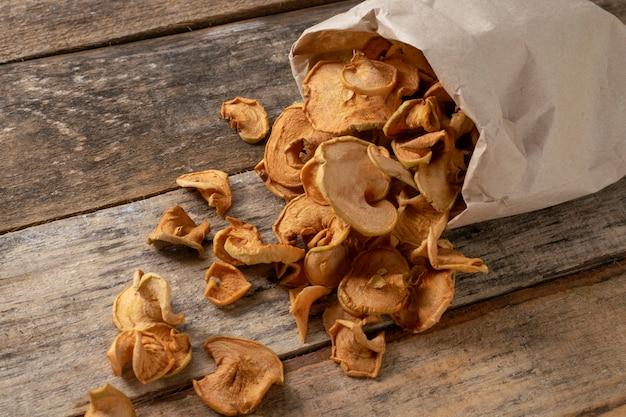 Chips chips de maçã de fruta em fundo de madeira. fatias de maçã secas.