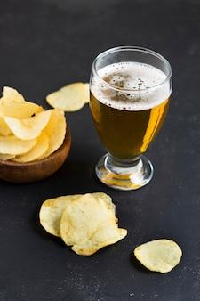 Chips de alto ângulo ao lado de vidro com cerveja