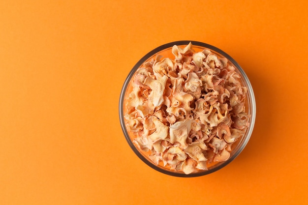 Chips de cenoura em uma tigela de vidro em um fundo laranja degradê. composição minimalista. alimentação saudável.