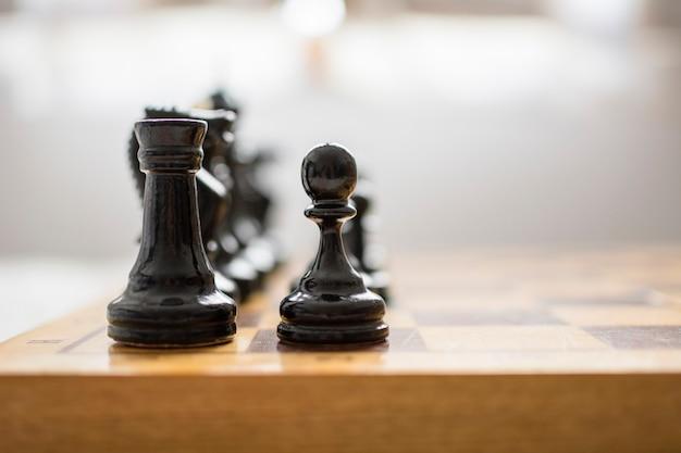 Chips de xadrez, em primeiro plano, um peão e uma torre preta, no tabuleiro, prontos para começar o jogo.