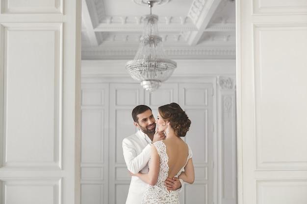 Chique casal de noivos e noiva posando em um estúdio branco