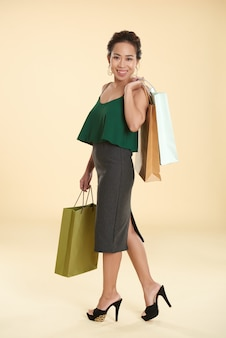 Chique jovem mulher asiática posando com sacolas de compras