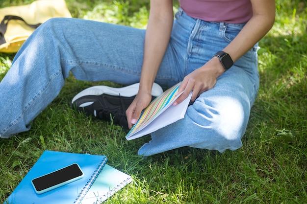 Chiqueiro no parque. uma mulher de pele escura sentada na grama e estudando