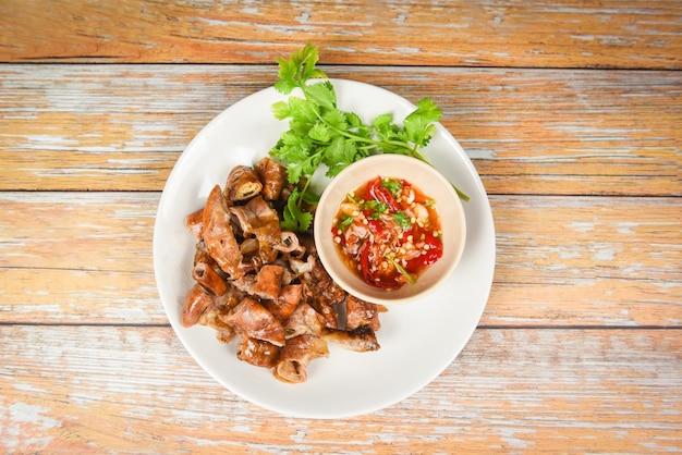 Chitterlings de porco assado com molho de pimenta picante - parte de intestinos entranhas de comida tailandesa asiática de porco