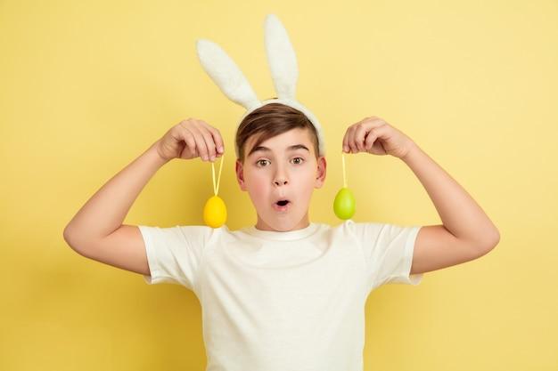 Chocado. a caça ao ovo está chegando. menino caucasiano como um coelhinho da páscoa em fundo amarelo do estúdio. saudações de páscoa feliz. lindo modelo masculino. conceito de emoções humanas, expressão facial, feriados. copyspace.