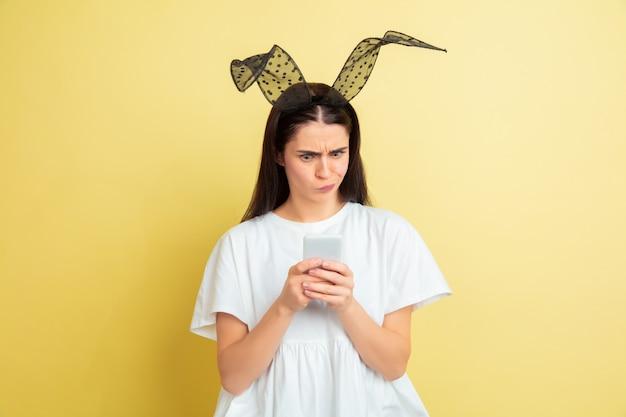 Chocado ao usar o telefone. mulher caucasiana como um coelhinho da páscoa em fundo amarelo.