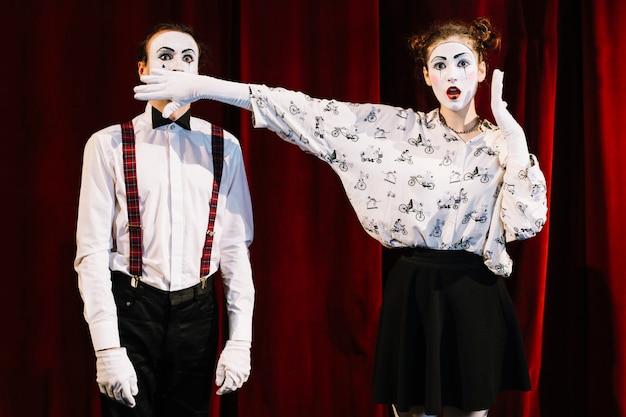 Chocado artista feminino mime cobrindo a boca do mime masculino em frente a cortina